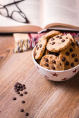 Chocolate chip cookies and book on wood background — Stock Photo