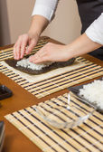 Woman chef filling japanese sushi rolls with rice — Stock Photo
