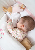Baby girl sleeping in a cot with pacifier and toy — Stock Photo