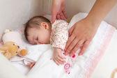 Hands of mother caressing her baby girl sleeping — Stockfoto