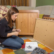 ������, ������: Girl reading instructions to assemble furniture