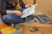 Girl reading instructions to assemble furniture — Stock Photo