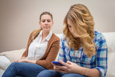 Suspicious mother spying a daughter looking phone — Stock Photo
