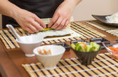 Hands of woman chef rolling up a japanese sushi — Foto Stock