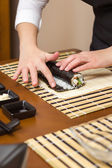 Woman hand moistening with water a sushi roll edge — Stok fotoğraf