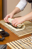Hands of woman chef rolling up a japanese sushi — Stockfoto