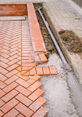 Orange brick paving stones in construction process — Stock Photo