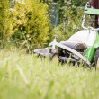 Senior man mowing the lawn with a lawnmower — Stock Photo