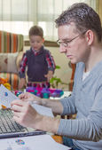 Father working in home office and son playing — Stock Photo