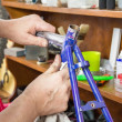 Hands of real bicycle mechanic sanding frame bike — Stock Photo #41585639