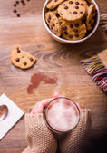 Kobiece ręce z gorącego napoju i czekoladowe ciasteczka — Zdjęcie stockowe