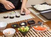 Closeup of woman chef putting japanese sushi roll — Stock Photo