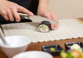 Closeup of woman chef cutting japanese sushi roll — Stock Photo