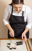 Portrait of woman chef cutting japanese sushi roll — Stock Photo