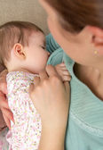 Young mother breast feeding her baby at home — Stock Photo