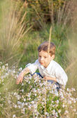 Happy cute kid picking flowers in a field — Stock Photo