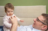 Happy father playing with cute baby in a sofa — Stock Photo
