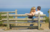 Back view of love couple sitting outdoors on bench — Stock Photo