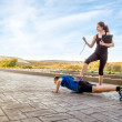 Girl coach training hard a man through push ups — Stock Photo #44444571