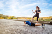 Girl coach training hard a man through push ups — Stockfoto