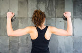 Back view of young girl lifting dumbbell discs — Fotografia Stock