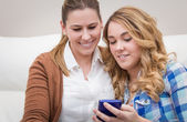Mother and daughter laughing when looking at phone — Stockfoto