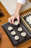 Woman chef placing japanese sushi rolls on a tray — Stock Photo