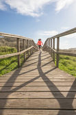 Back view of girl running in a wood boardwalk — Stock Photo