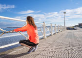 Young girl warming before running in a promenade — Stock Photo