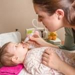 Постер, плакат: Mother cleaning mucus of baby with nasal aspirator