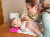 Mother cleaning mucus of baby with nasal aspirator — Stock Photo