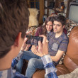 Friend taking photos to teenage couple on a sofa — Stock Photo #46443051