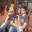 Friend taking photos to teenage couple on a sofa — Stock Photo