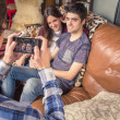 Friend taking photos to teenage couple on a sofa — Stock Photo #46443775