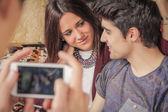 Garoto mãos tirando fotos de casal adolescente no sofá — Fotografia Stock