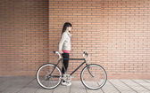 Sportive woman with fixie bike over a brick wall — ストック写真