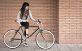Sportive woman with fixie bike over a brick wall — Stock Photo