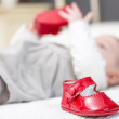 Baby red shoes and babe playing on the background — Stock Photo