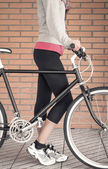 Customized fixie bike and woman over brick wall — Stock Photo