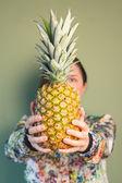Мода девушка держит ананас перед лицом — Стоковое фото