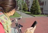 Sportive woman with fixie bike looking smartphone — Foto de Stock