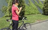 Sportieve vrouw met fixie fiets op zoek smartphone — Stockfoto