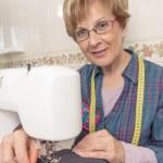Senion seamstress woman working on sewing machine — Stock Photo #48308761