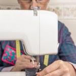 Senion seamstress woman working on sewing machine — Stock Photo #48309533