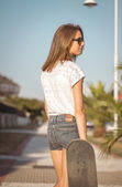 Young girl with a skateboard outdoor — Stock Photo