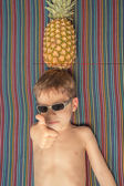 Happy child with sunglasses and pineapple in head — Stockfoto