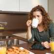 Tired young girl with cup of coffee in a breakfast — Stock Photo #48709733