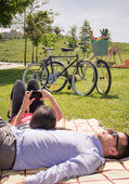 Girl using smartphone lying over man on the park — Stock Photo