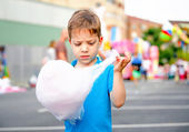 Cute kid eating cotton candy over fair background — Stock Photo