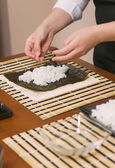 Hands of woman chef filling japanese sushi rolls with rice — Stock Photo